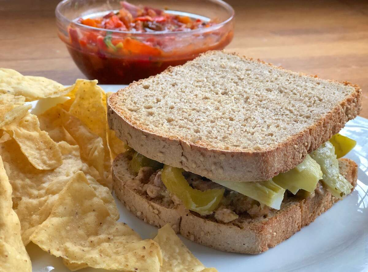 Sandwich made with sourdough sandwich bread on a plate, chips and salsa on the side.