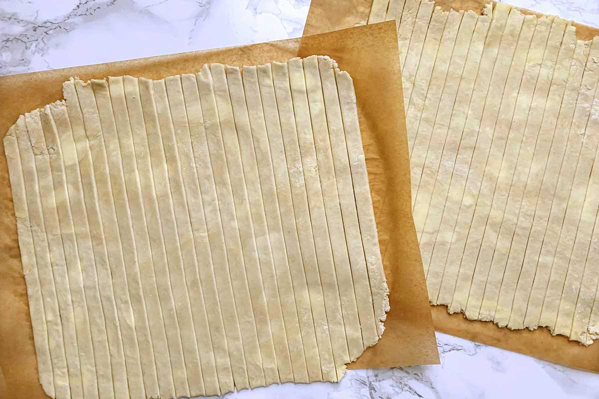 Two square sheets of rolled dough, cut into vertical strips