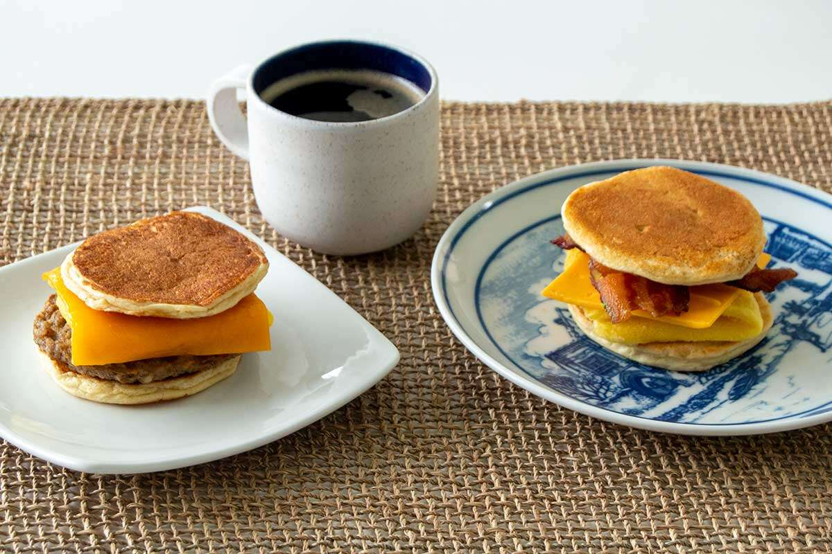 Two breakfast sandwiches made with pancakes as bread -- one with sausage, the other with bacon