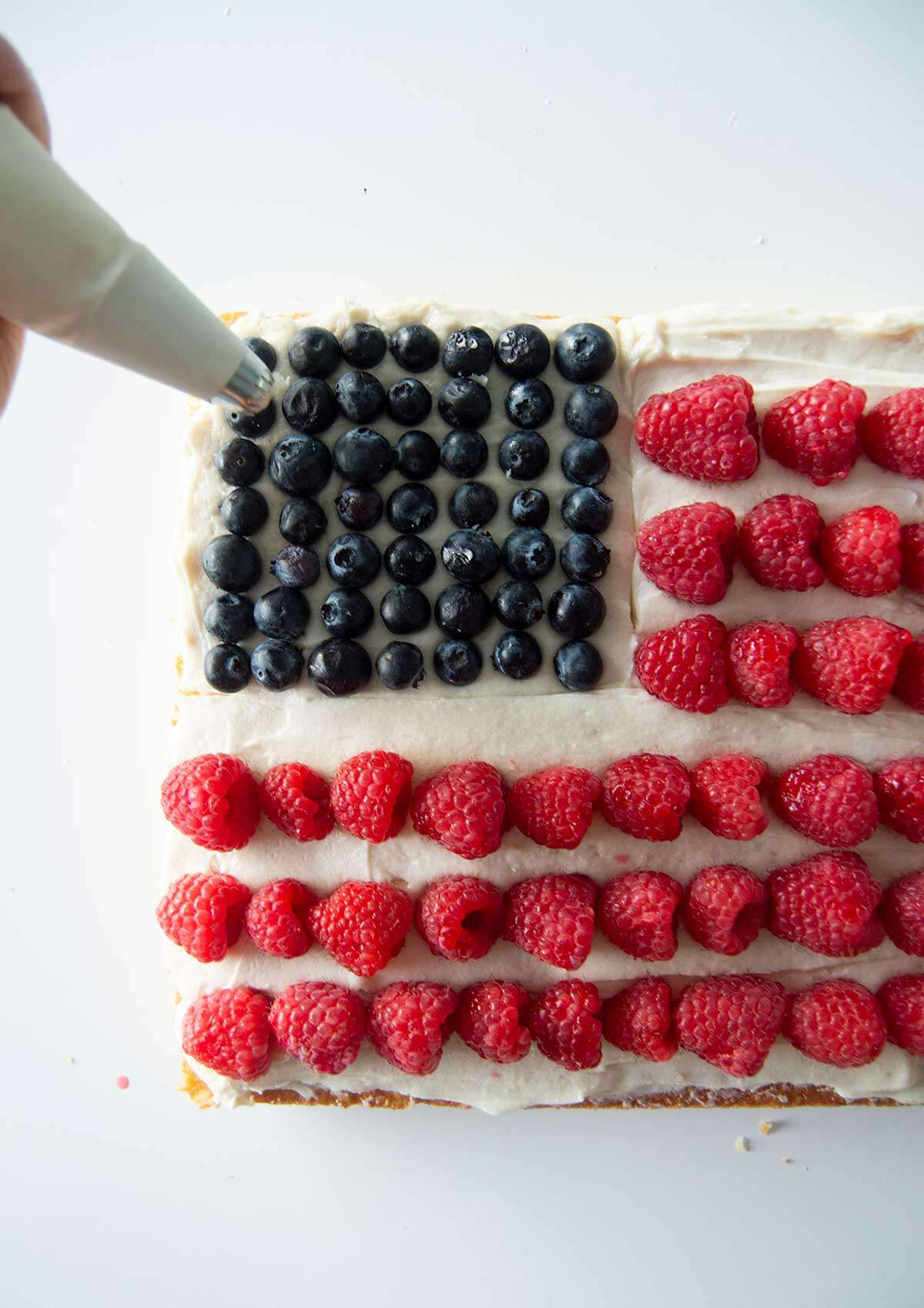 Hand piping stars on flag cake