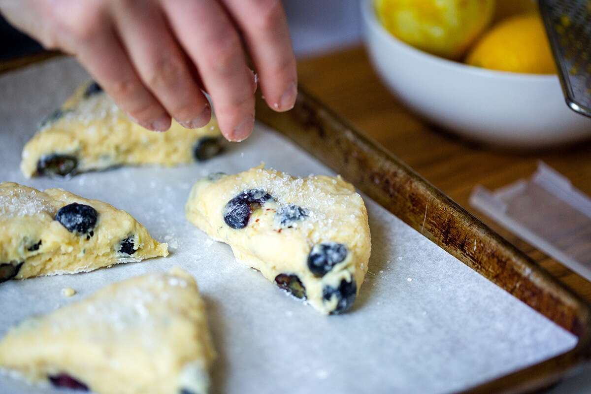 A baker's hand sprinkling unbaked blueberry scones with sparkling sugar on a baking sheet