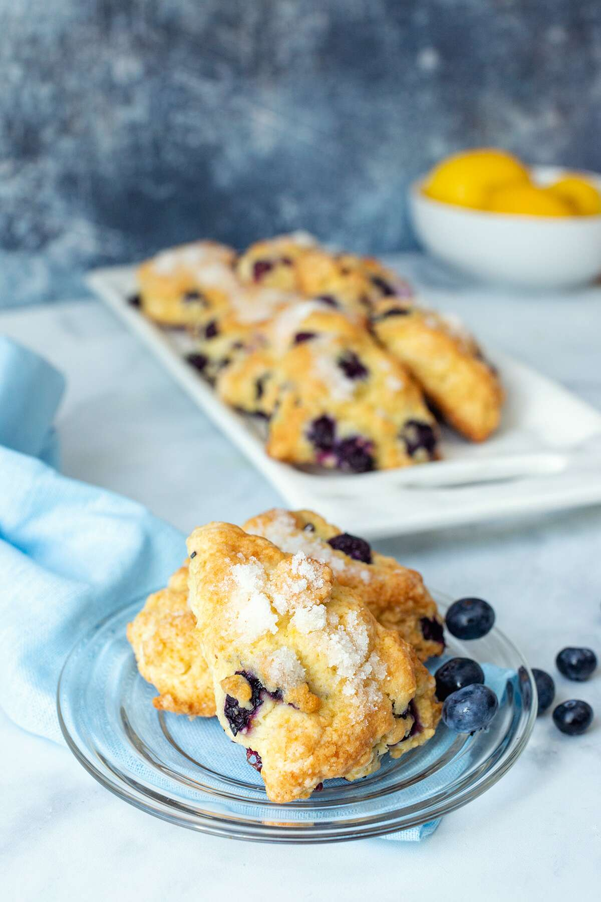 Fresh blueberry scones on a platter next to a bowl of lemons with two scones on a plate, ready for serving