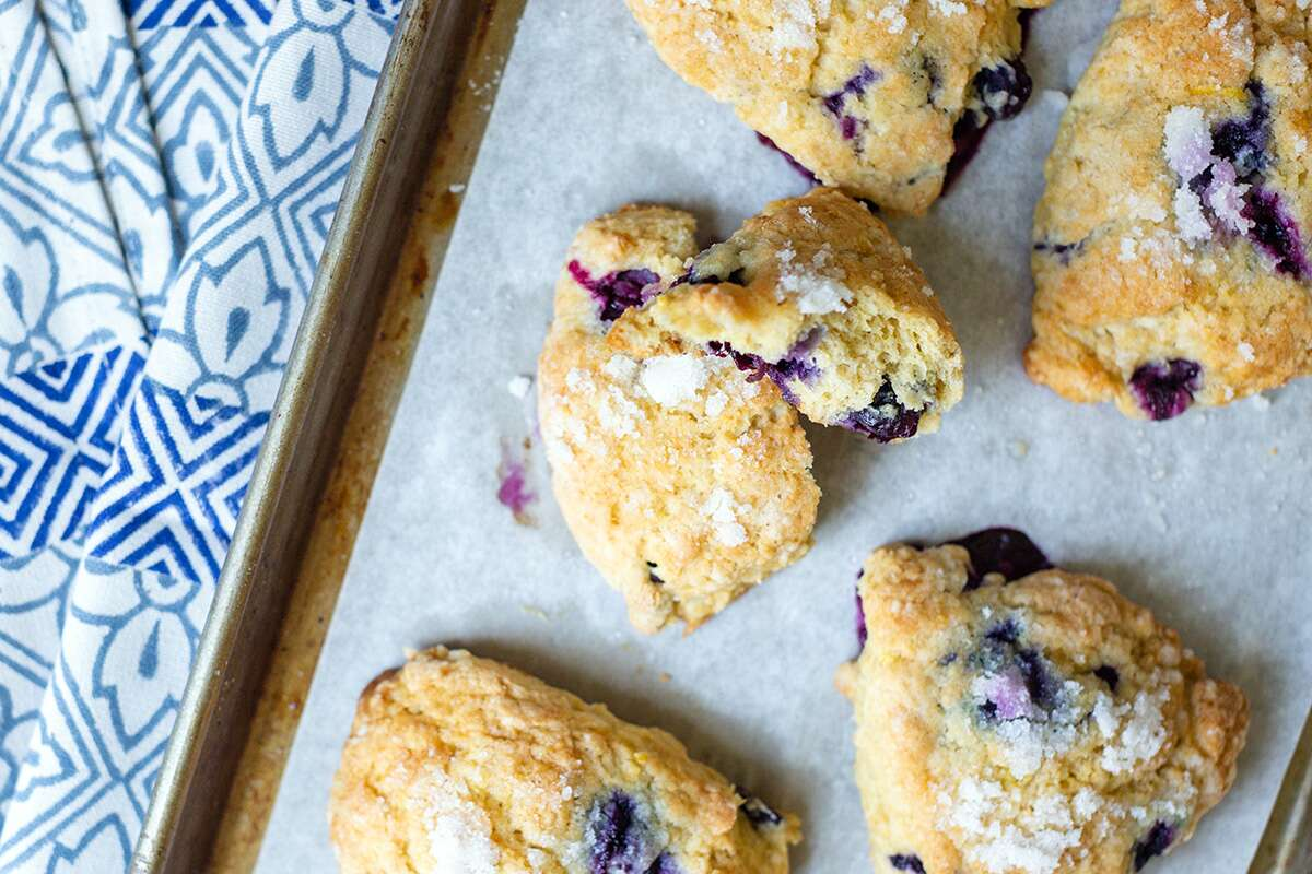 Whole wheat blueberry scones on a baking sheet with one broken open to show the texture