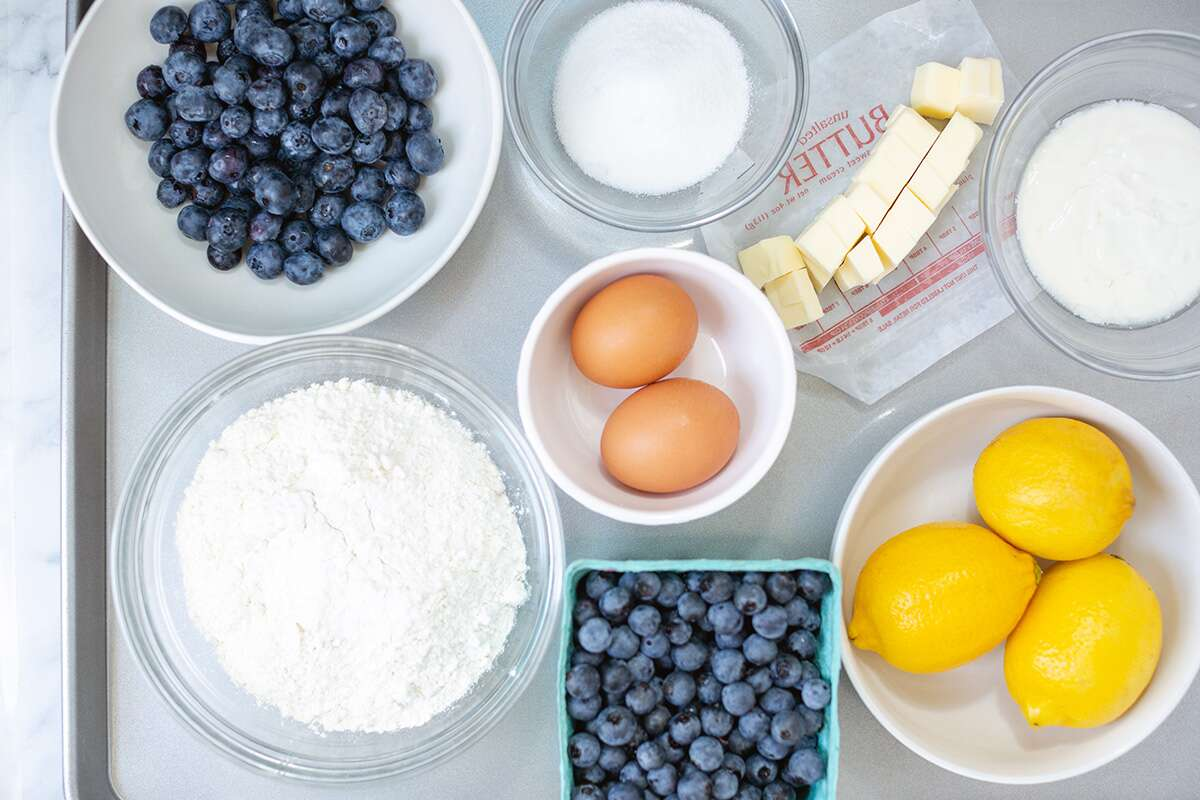Small bowls of ingredients for Fresh Blueberry Scones on a tray including butter, sugar, flour, blueberries, and lemons