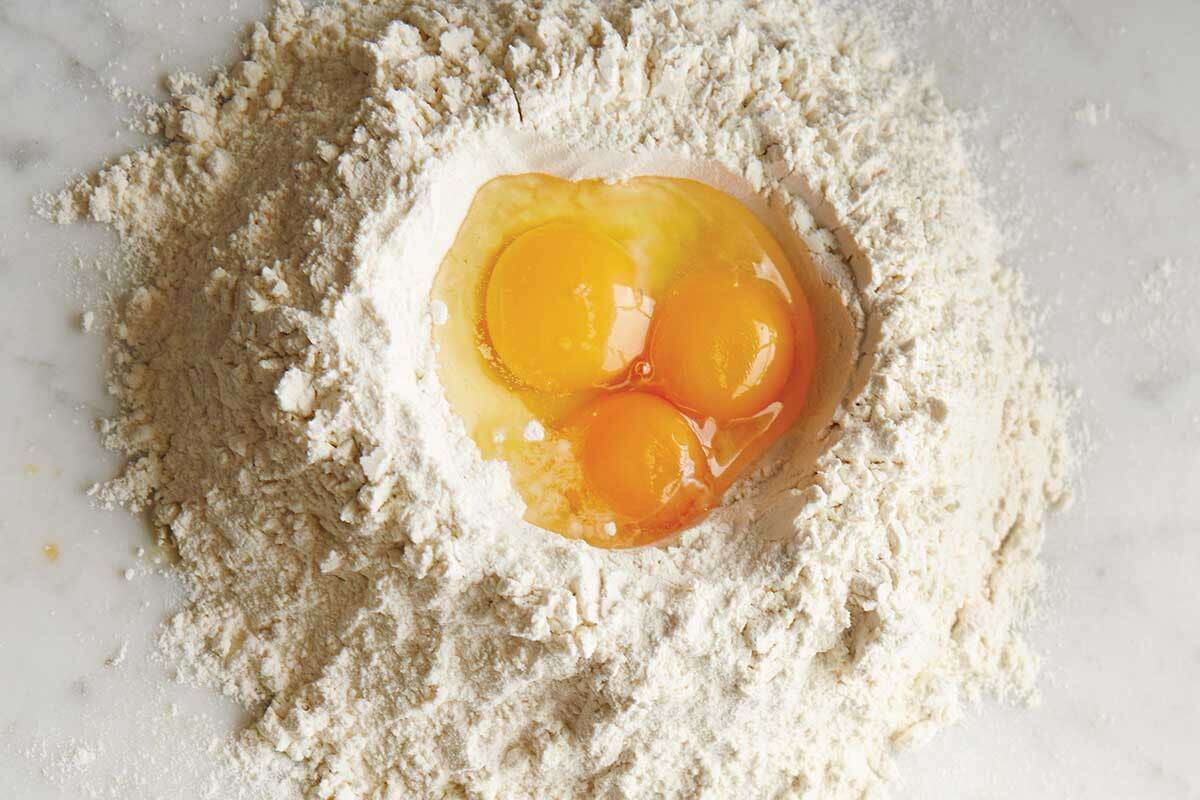 Three eggs cracked into the middle of a pile of pasta flour, about to be mixed into dough