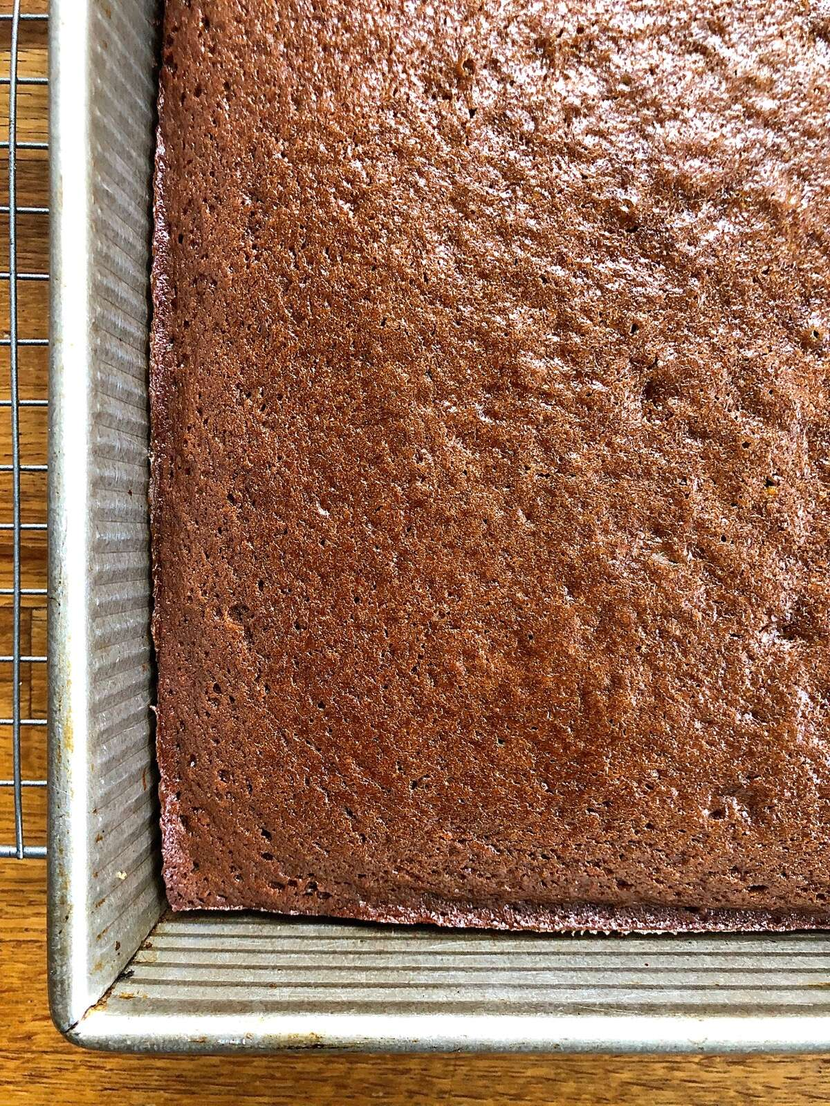 Baked gingerbread in a pan, edges just pulling away from the sides of the pan.
