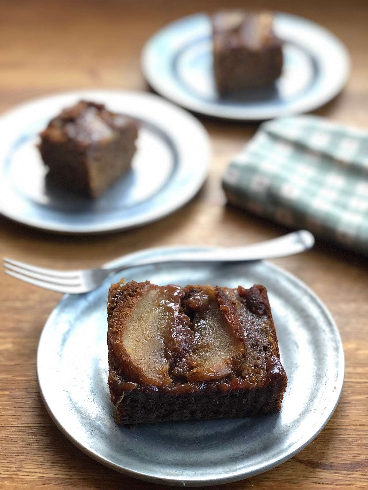 Square of apple upside-down gingerbread cake on a plate