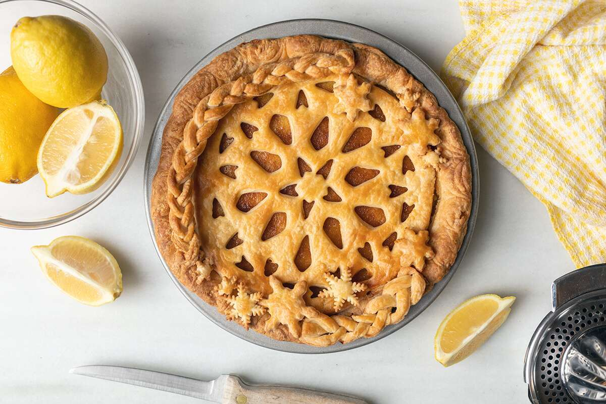 A lemon chess pie topped off with an intricate top crust on a kitchen table