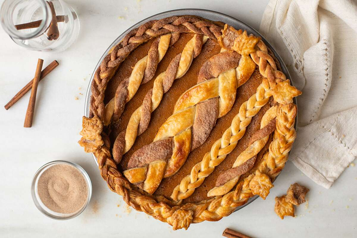 A pumpkin pie with braided strips and cinnamon-twists on top for decoration