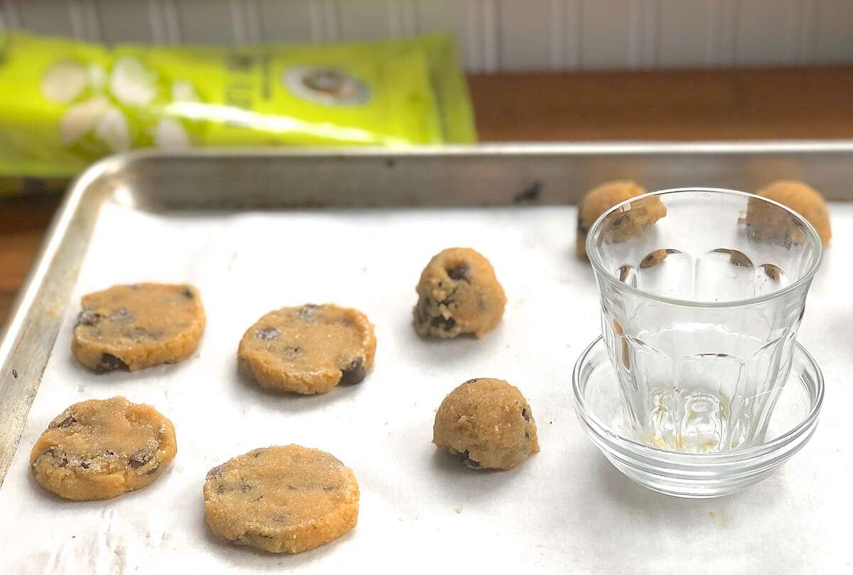 Dough for Gluten-Free Almond Flour Chocolate Chip Cookies flattened on a  baking sheet using the bottom of a drinking glass.