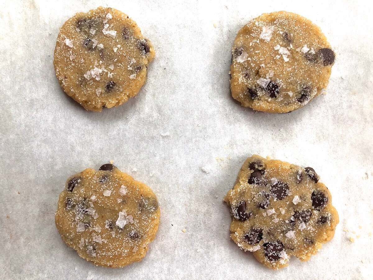 Dough for Gluten-Free Almond Flour Chocolate Chip Cookies scooped onto a baking sheet, flattened, and sprinkled with flaked sea salt before baking.