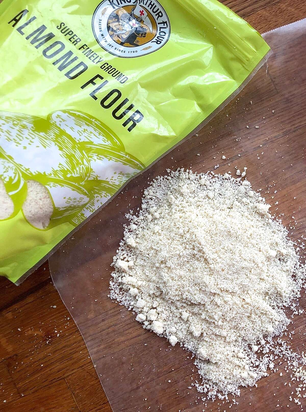 Bag of King Arthur Almond Flour, some spilled out onto a cutting board.