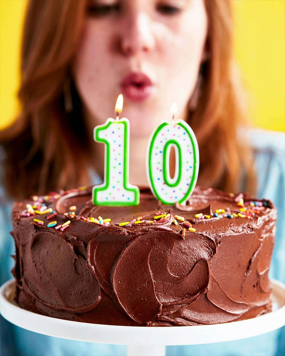 A woman blowing out the candles on a birthday cake with the number 10 on it