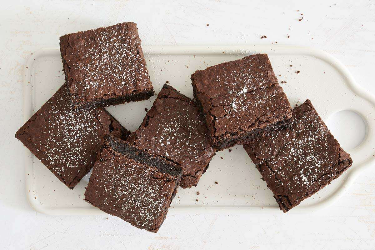 A platter of gluten-free brownies dusted with confectioners' sugar