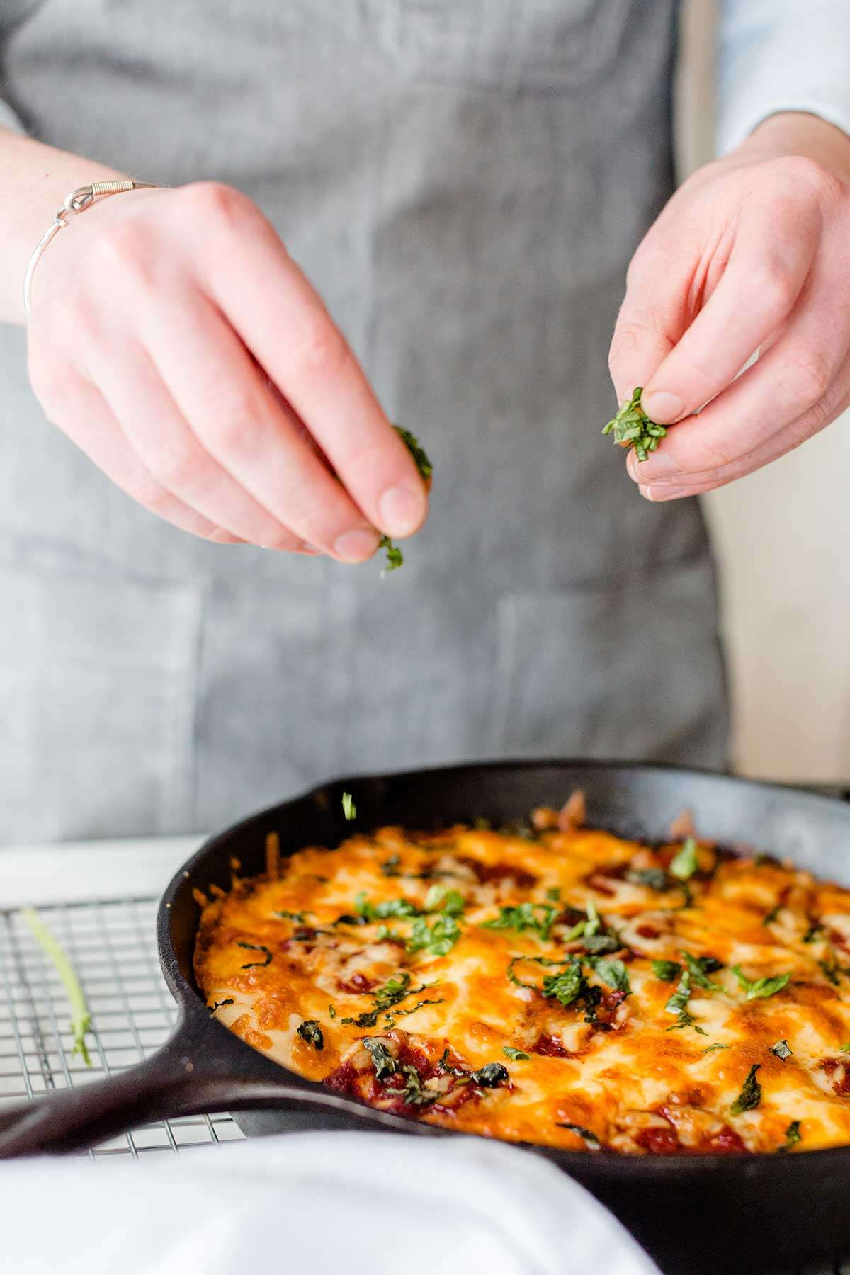 A baker sprinkling fresh herbs on top of a gluten-free pan pizza baked in a cast iron pan
