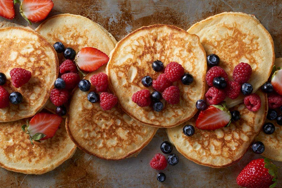 A tray of gluten-free pancakes topped with fresh berries