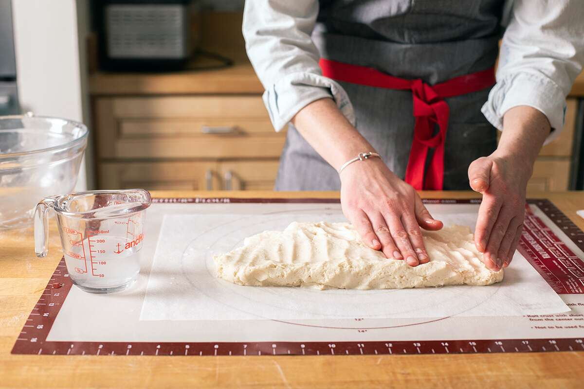 "A baker patting out gluten-free cinnamon roll dough into an 8"" x 16"" rectangle"