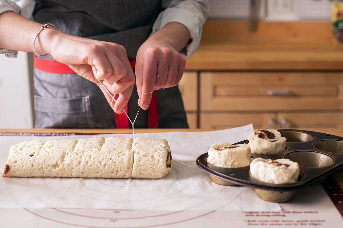 A baker using dental floss to slice a log of cinnamon roll dough into 8 pieces