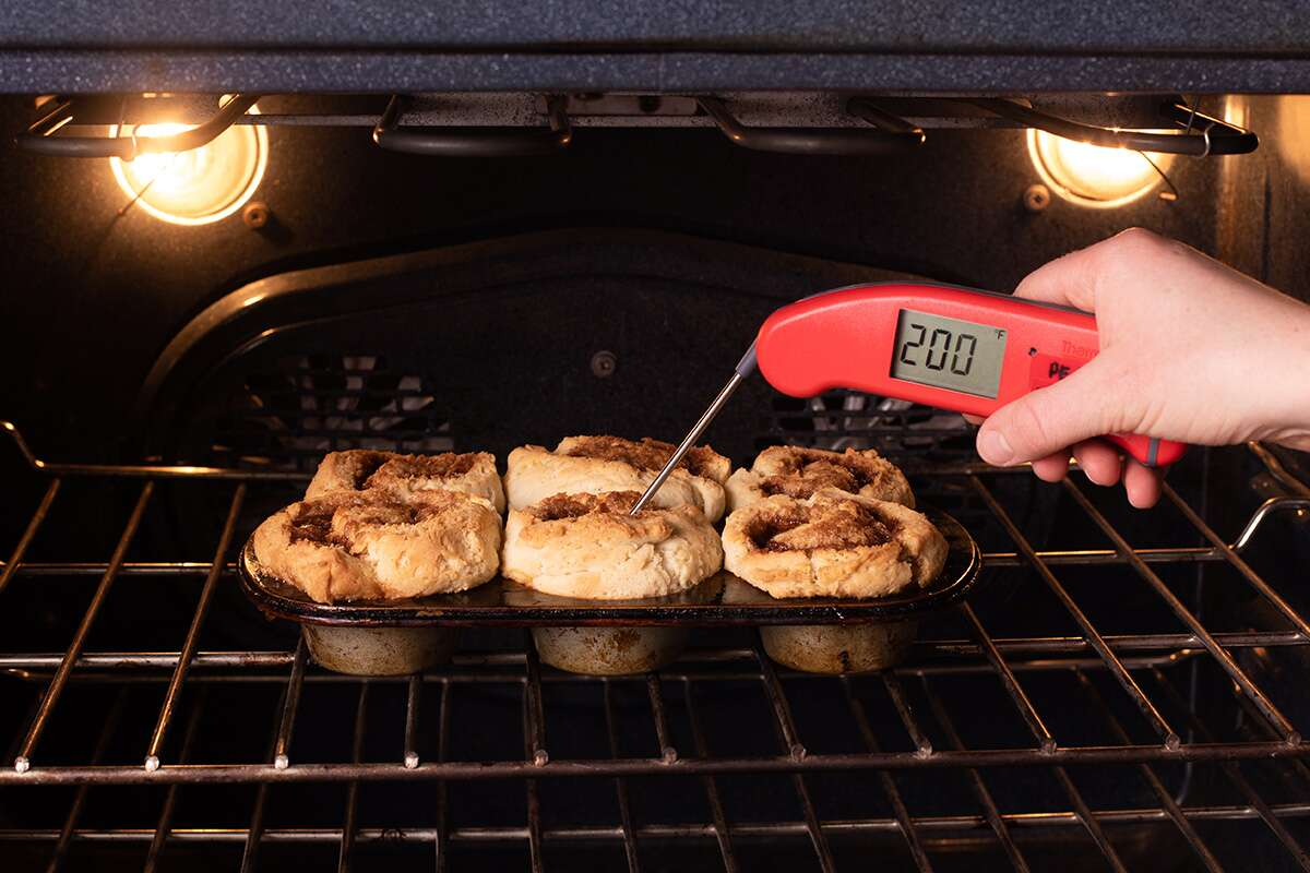 A baker testing the temperatuer of gluten-free cinnamon rolls baking in the oven, showing that it's about 200 degrees F