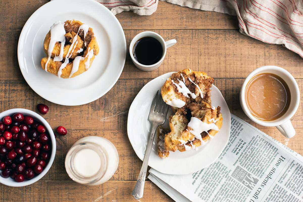 A breakfast scene complete with two plates of gluten-free cinnamon rolls and coffee