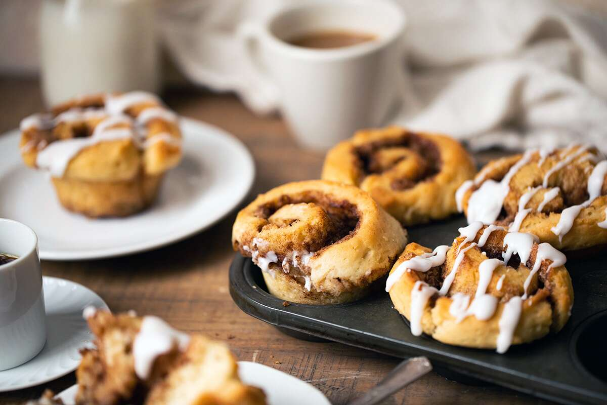Gluten-free cinnamon rolls on a tray next to a cup of coffee and plate with a cinnamon roll, ready to be enjoyed
