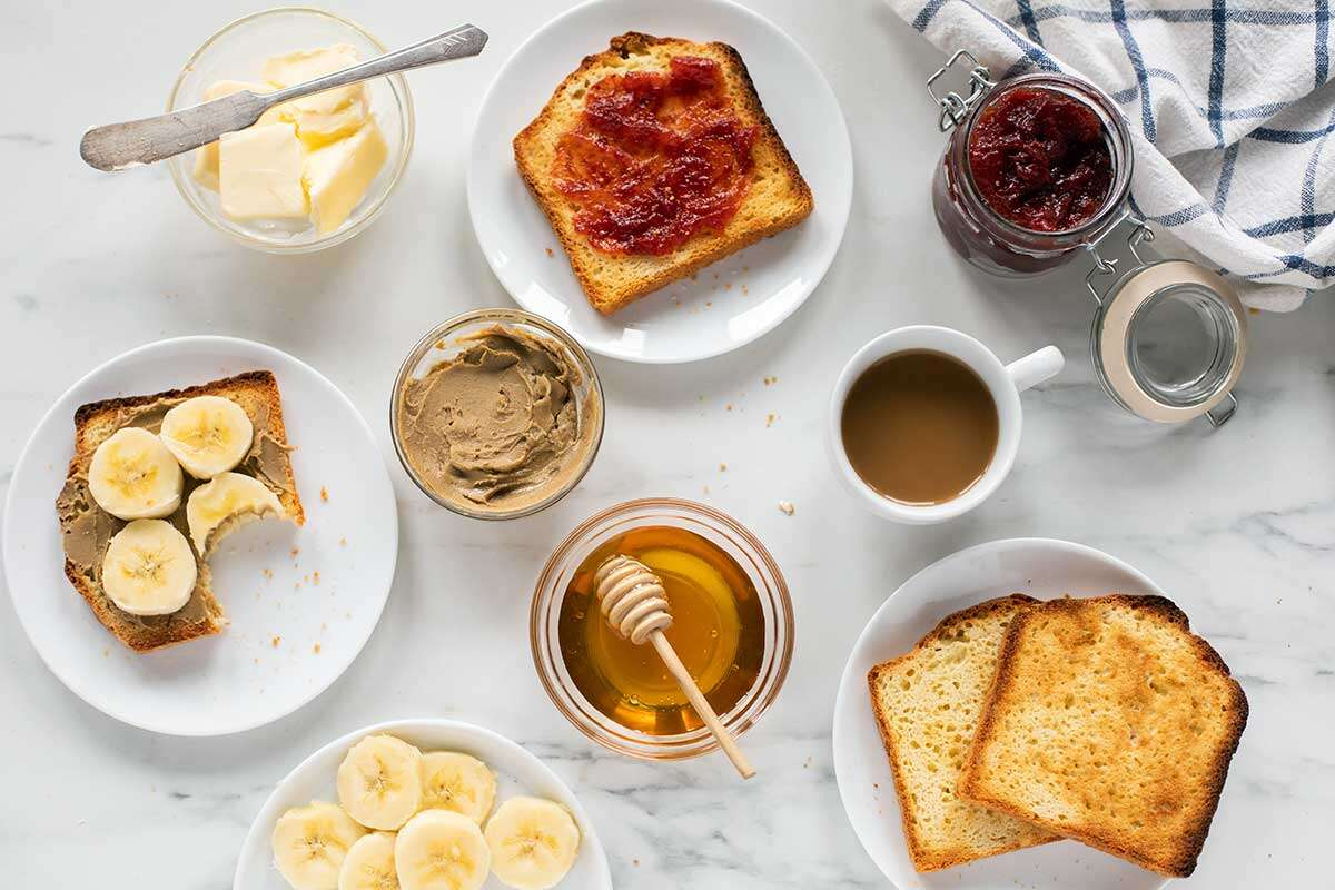 A kitchen table set for breakfast with gluten-free toast, honey, bananas, nut butter, and jam