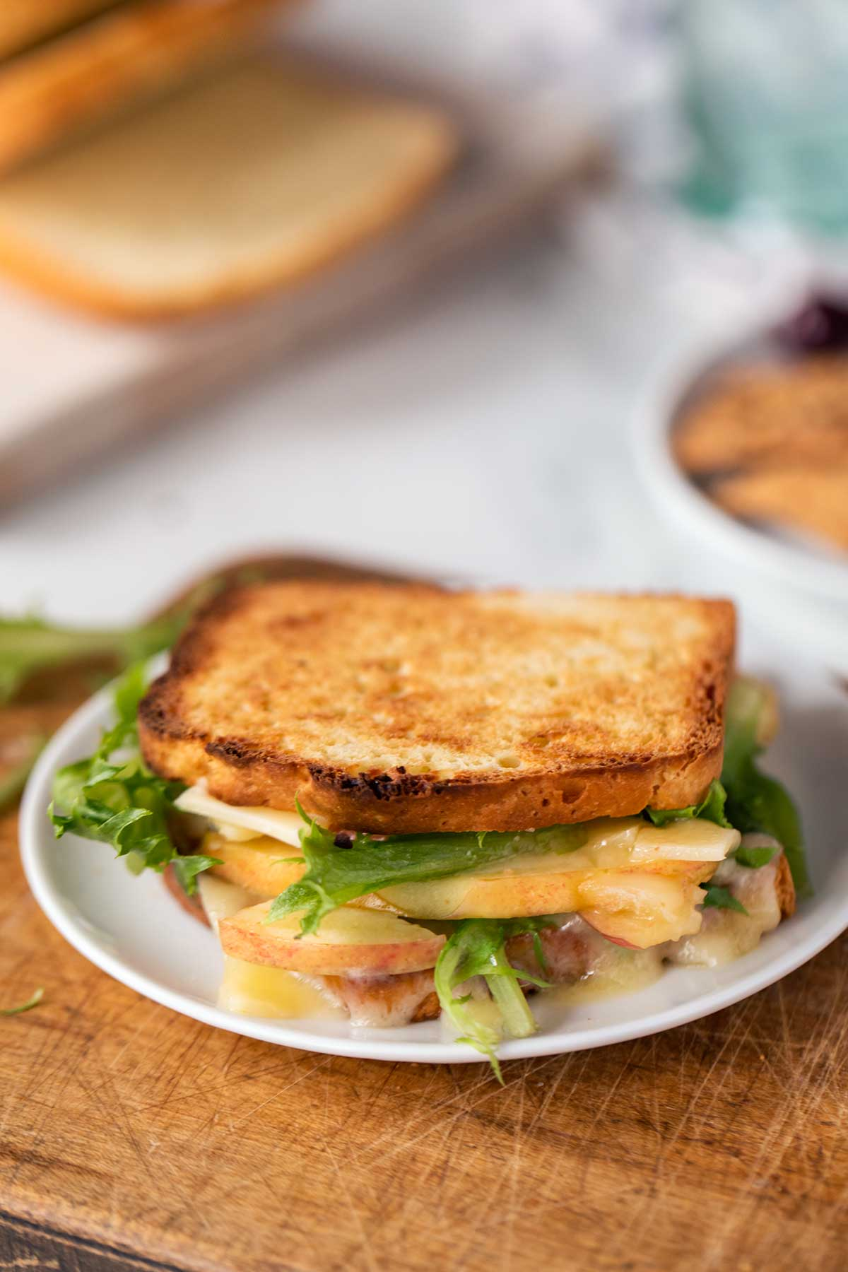 A grilled cheese made with gluten-free bread and garnished with slices of apples and greens