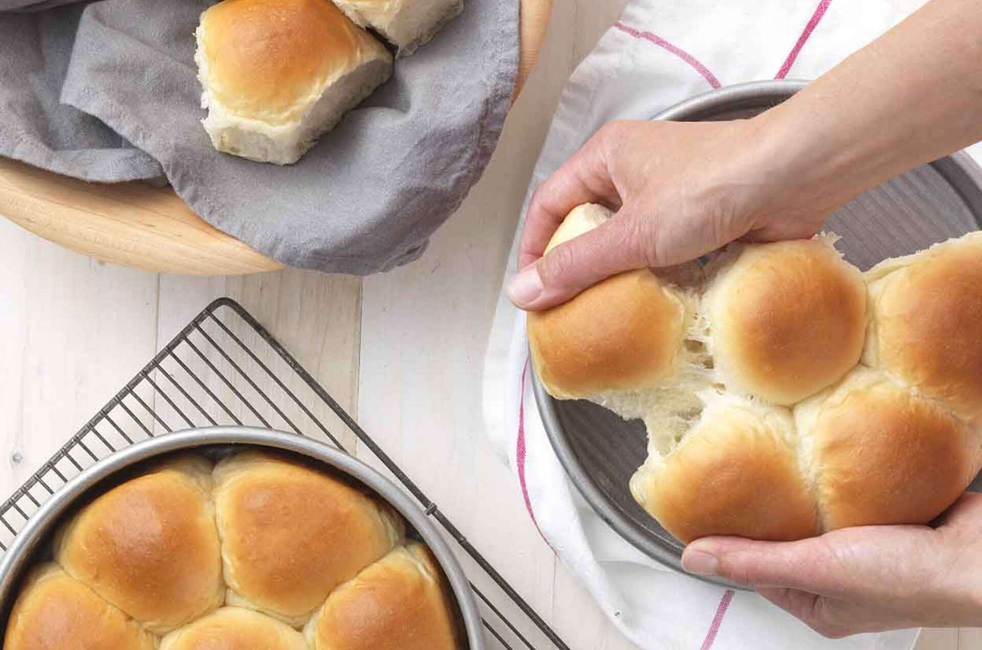 Hands pulling apart Golden Pull-Apart Buns from the pan