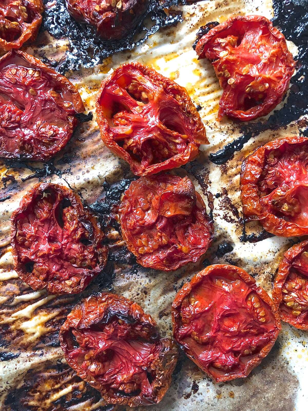 Sliced fresh tomatoes, char-roasted on a parchment-lined baking sheet.