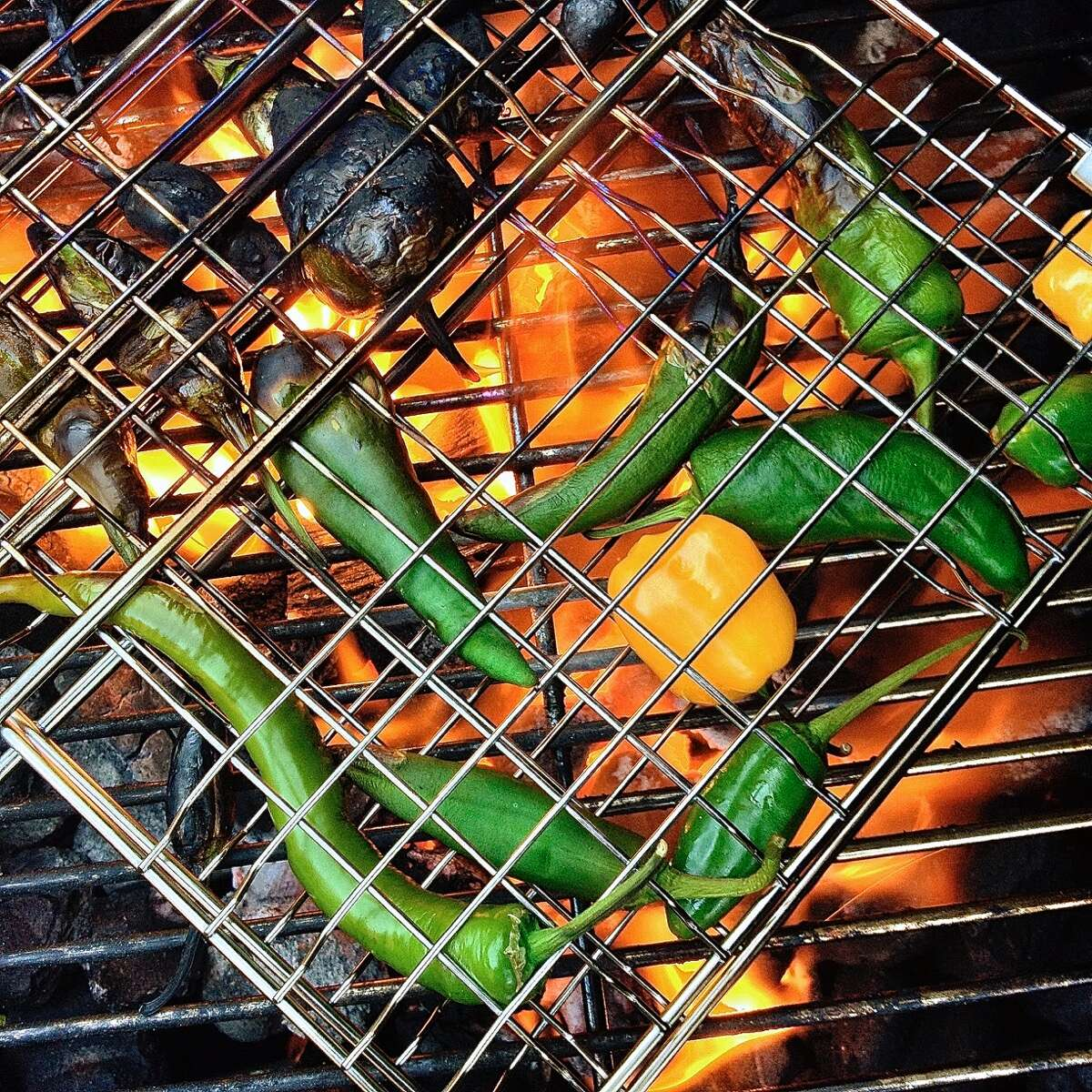 Serrano peppers and small yellow bell peppers charring on an open-flame grill.