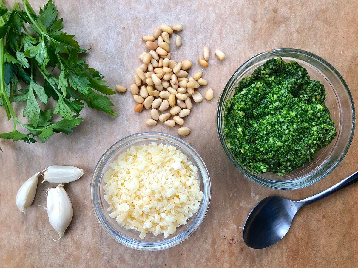 Ingredients for parsley pesto laid out on a table.