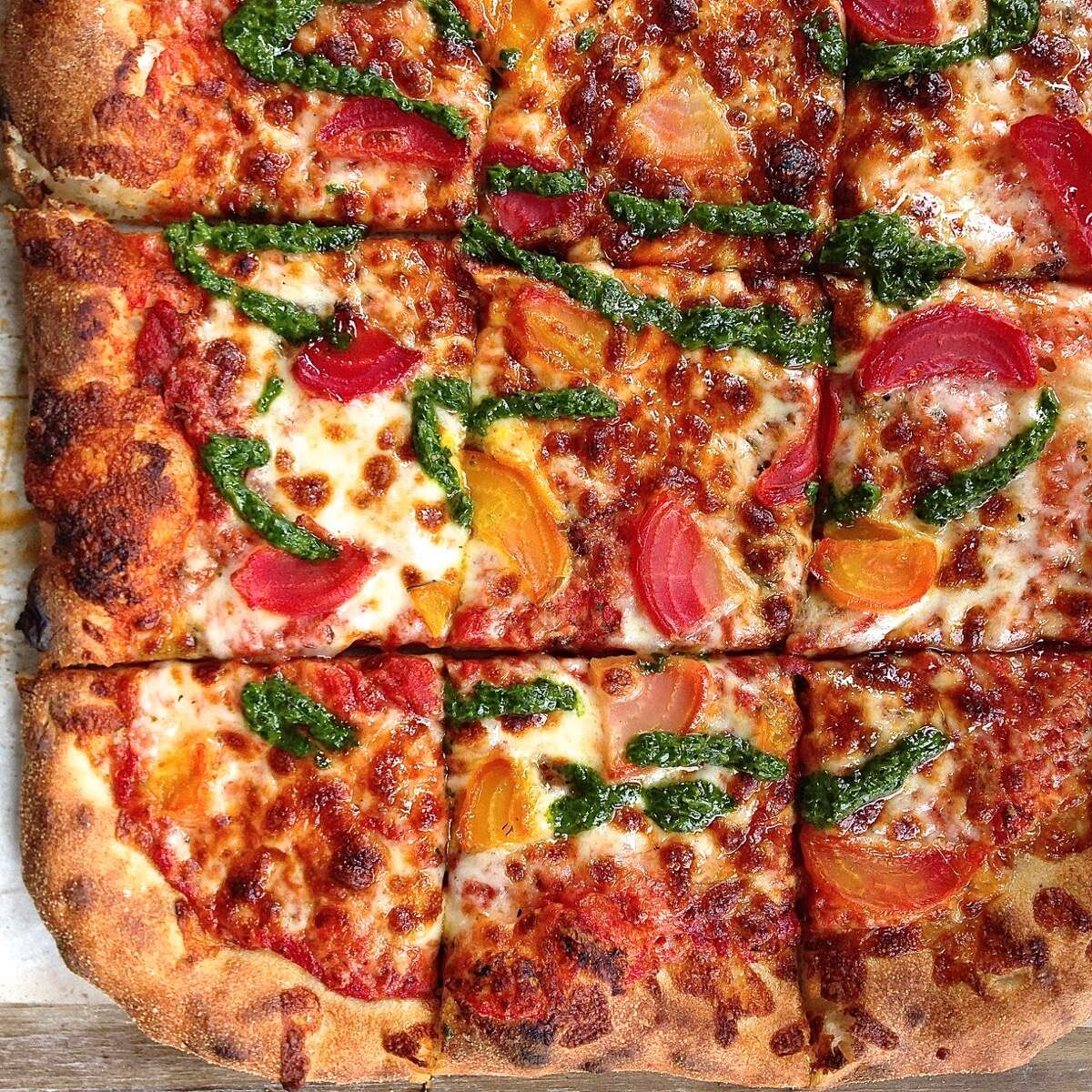 A square Sicilian-style pizza topped with golden beets, tomato sauce and cheese and drizzled with parsley pesto.