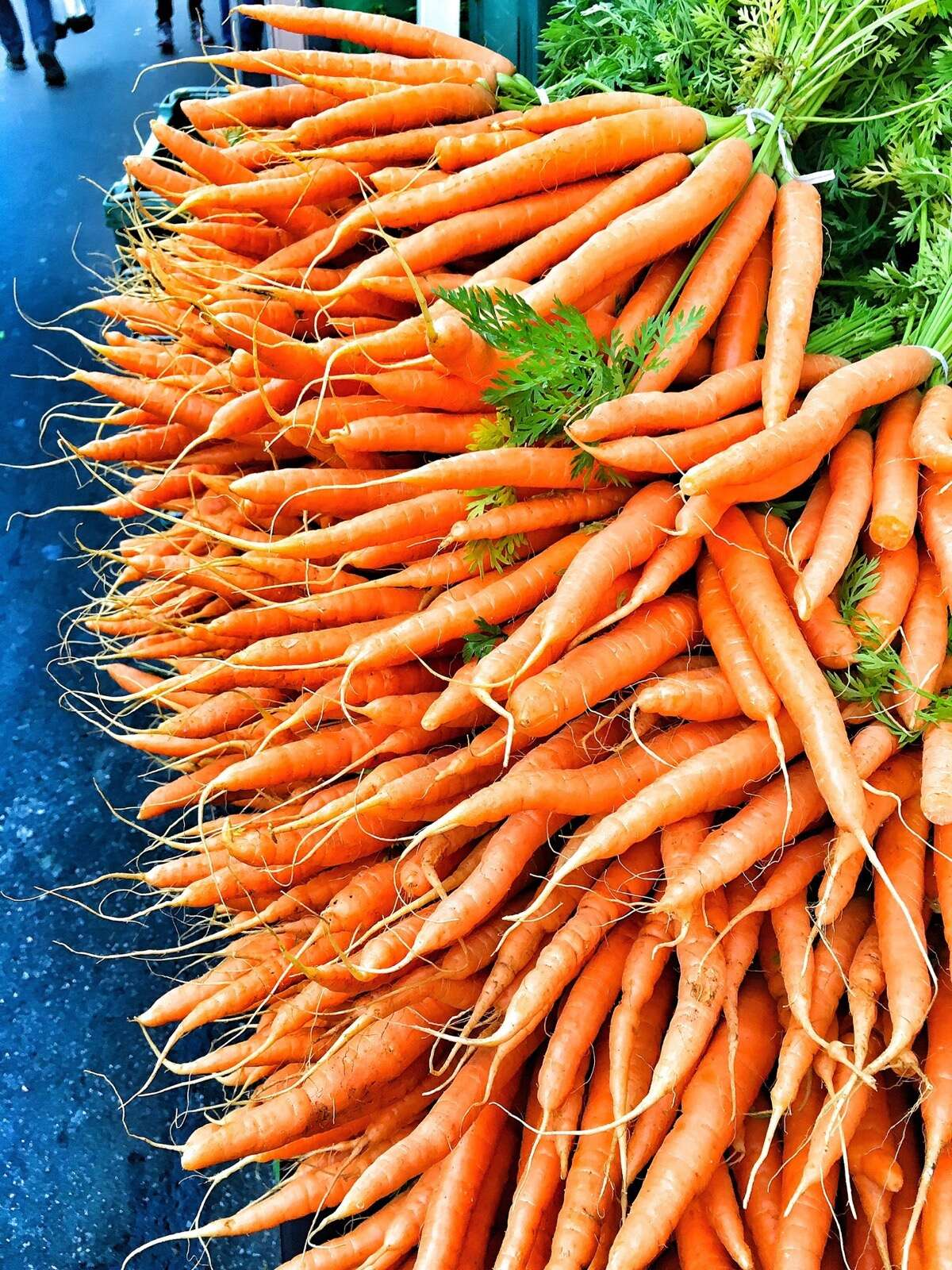 Bunches of thin carrots stacked on a stand at a farmers' market.