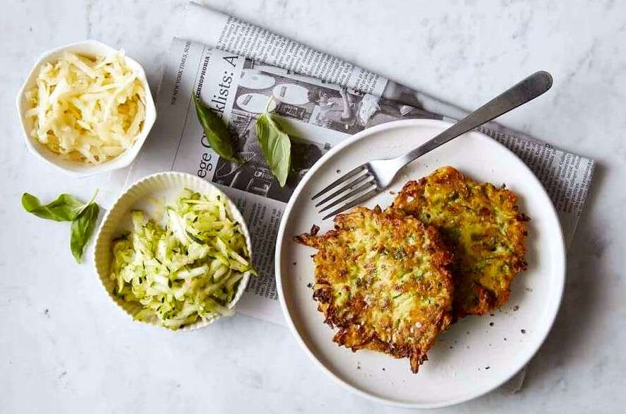 Zucchini pancakes on a plate, with shredded zucchini and grated cheese pictured on the side.