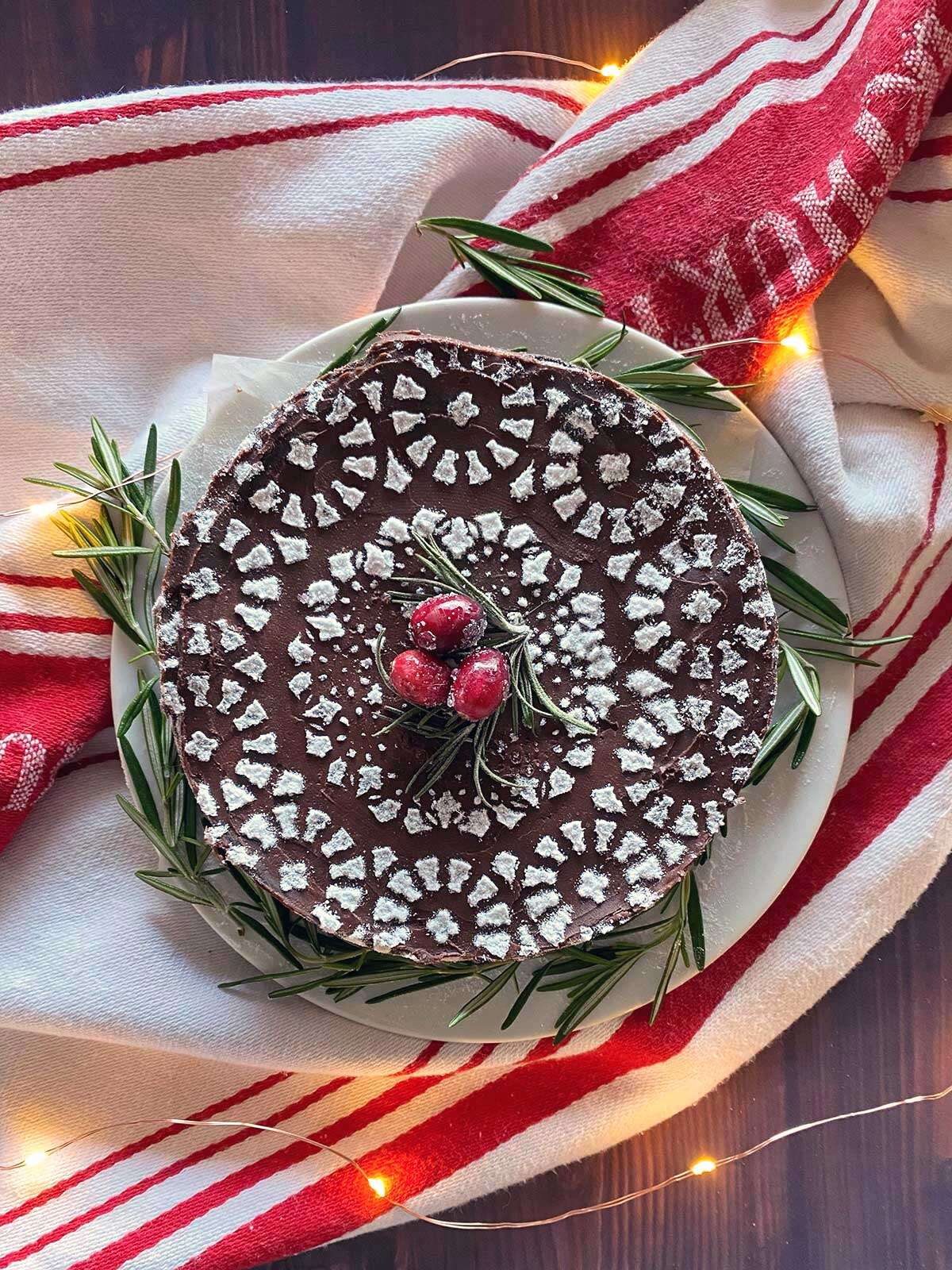 A flourless chocolate cake dressed up with a stenciled design on top and sugared cranberries for garnish