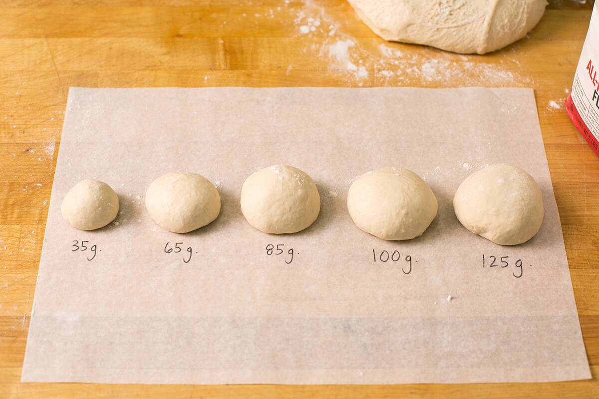 A line up of dough balls of different sizes ranging from 35 grams to 125 grams