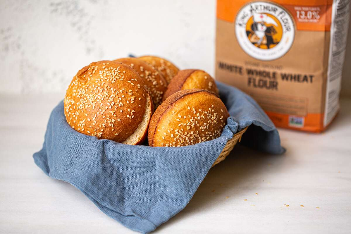 A basket of whole wheat hamburger buns and a bag of King Arthur White Whole Wheat Flour