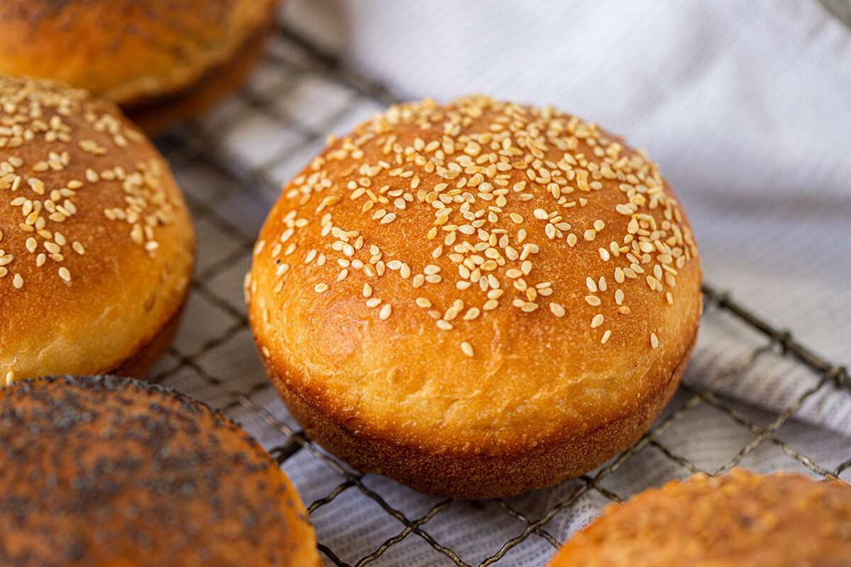 Homemade hamburger buns with a variety of toppings cooling on a rack