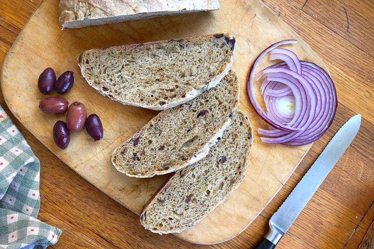 Greek Olive and Onion Bread sliced on a cutting board, with kalamata olives and red onion