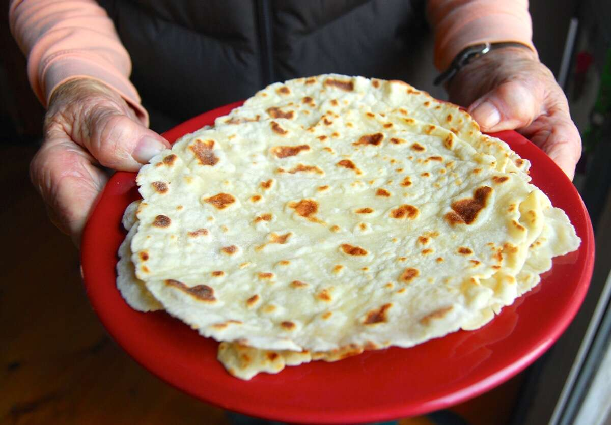 Hands holding a plate of lefse.