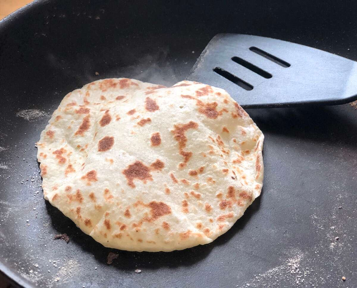 Lefse cooking in a frying pan