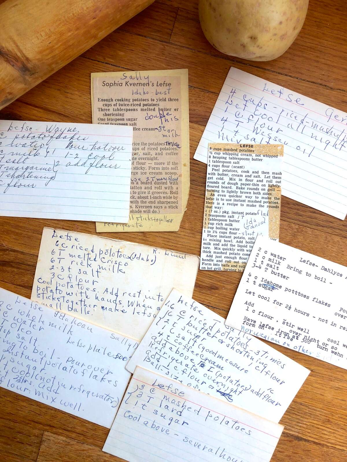 Recipe cards for lefse scattered on a kitchen table.