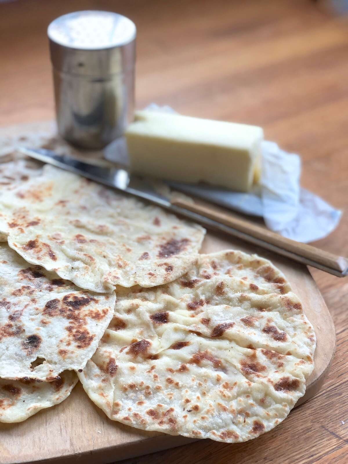 Cooked lefse fanned out on a cutting board, butter and cinnamon sugar in the background.
