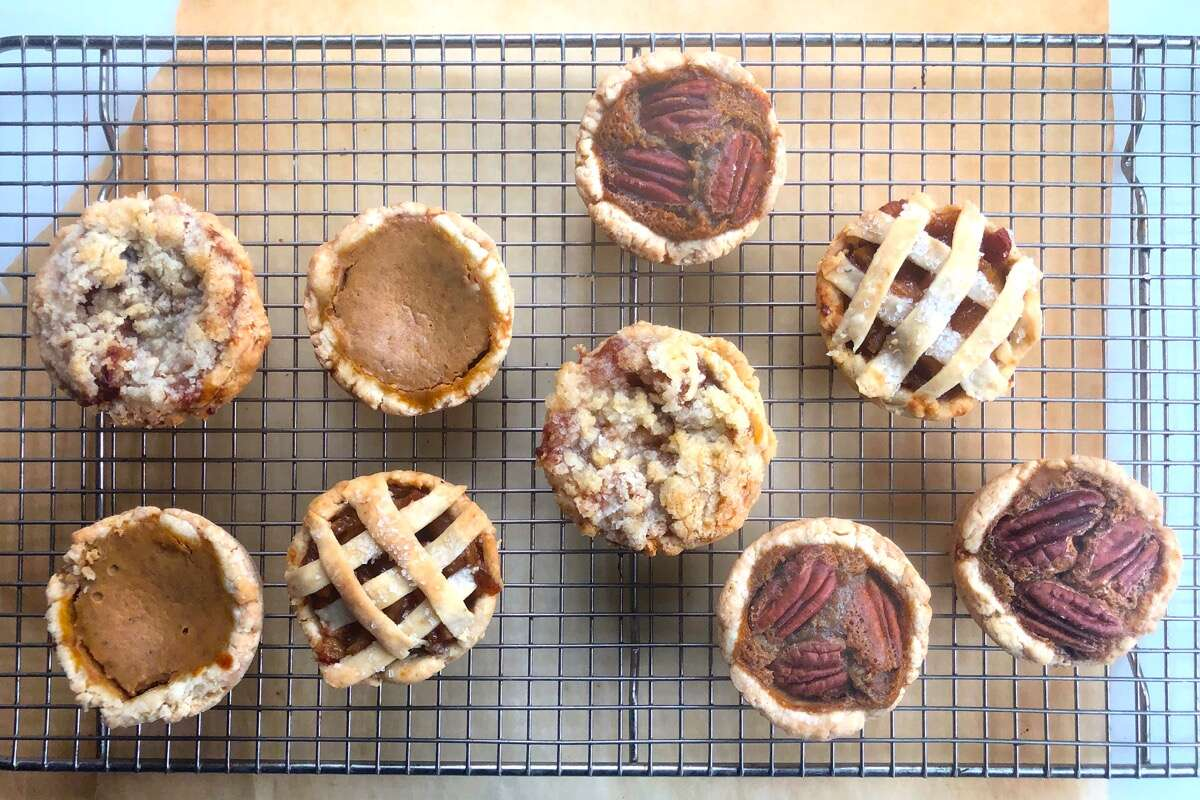 Mini pies — apple, pumpkin, and pecan — on a cooling rack.