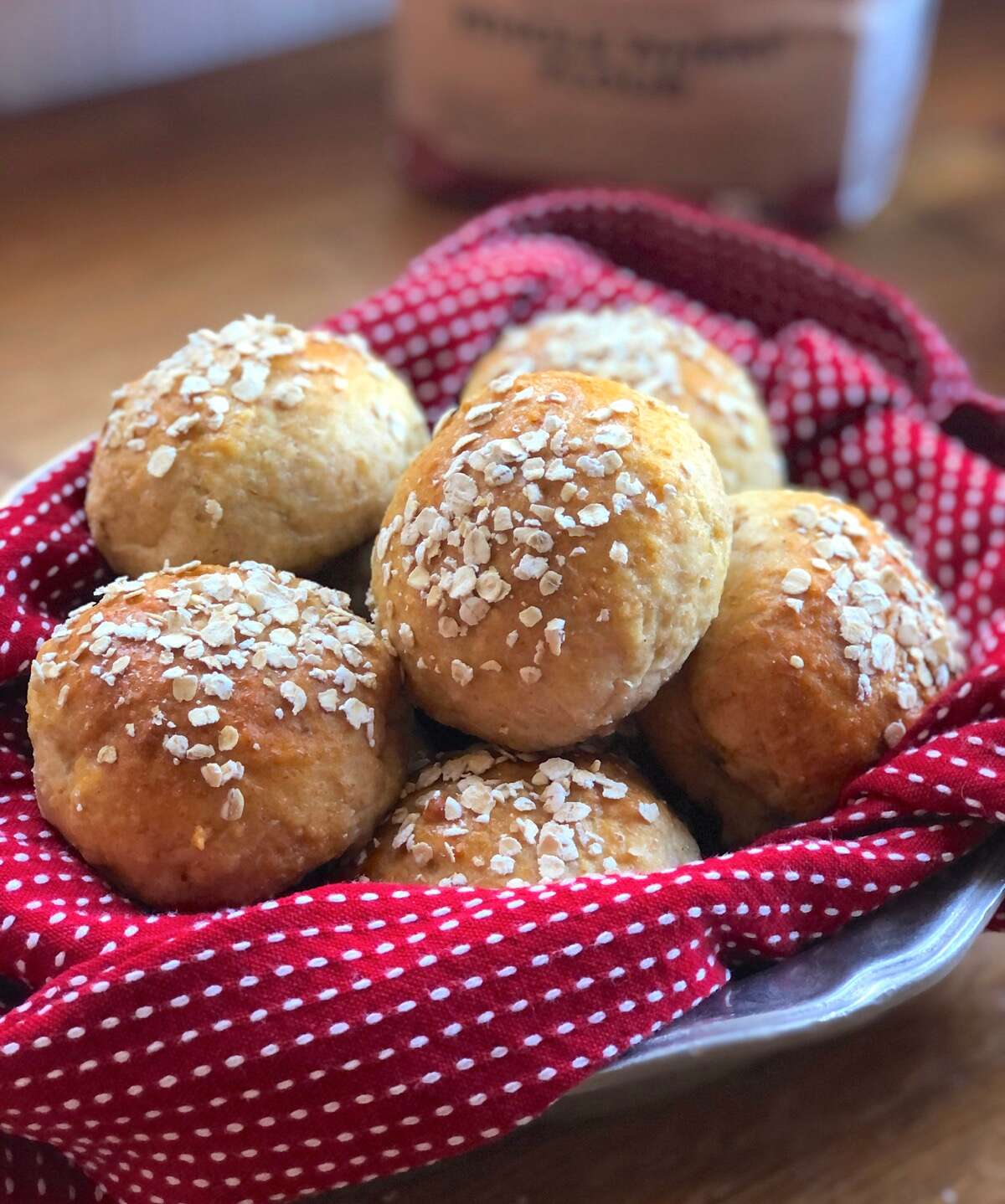Whole grain dinner rolls in a bowl lined with a red towel