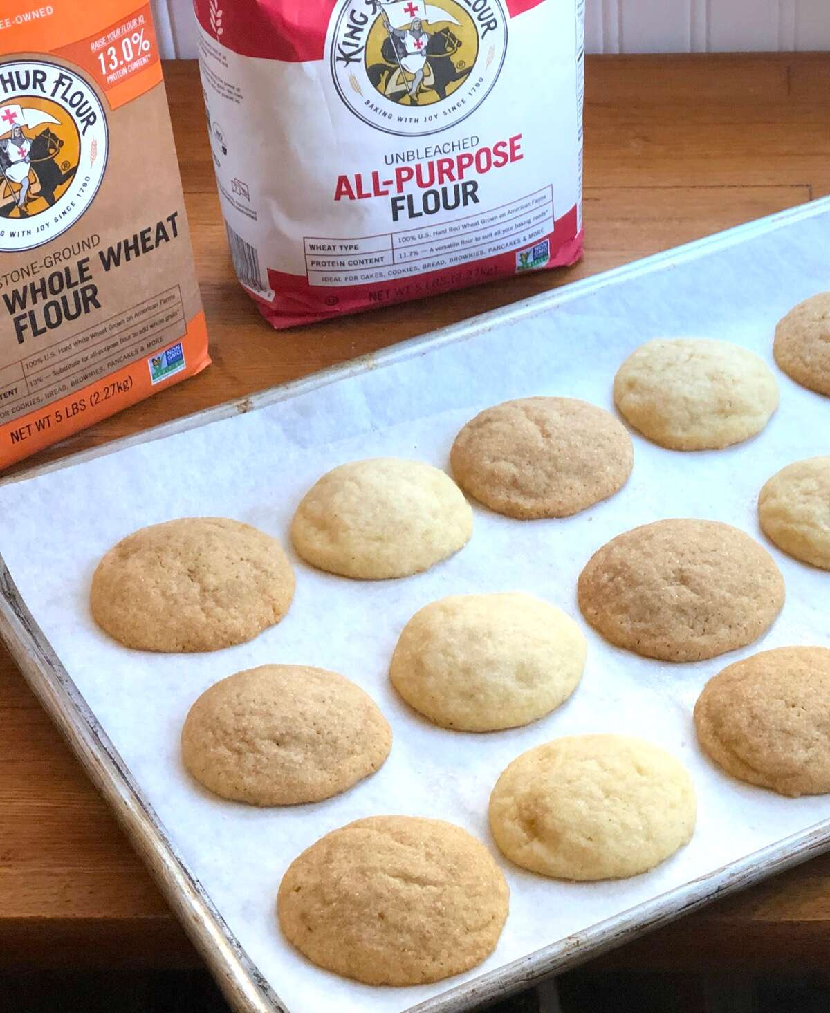 Sugar cookies n a baking sheet, half made with whole wheat flour, half with all-purpose flour.