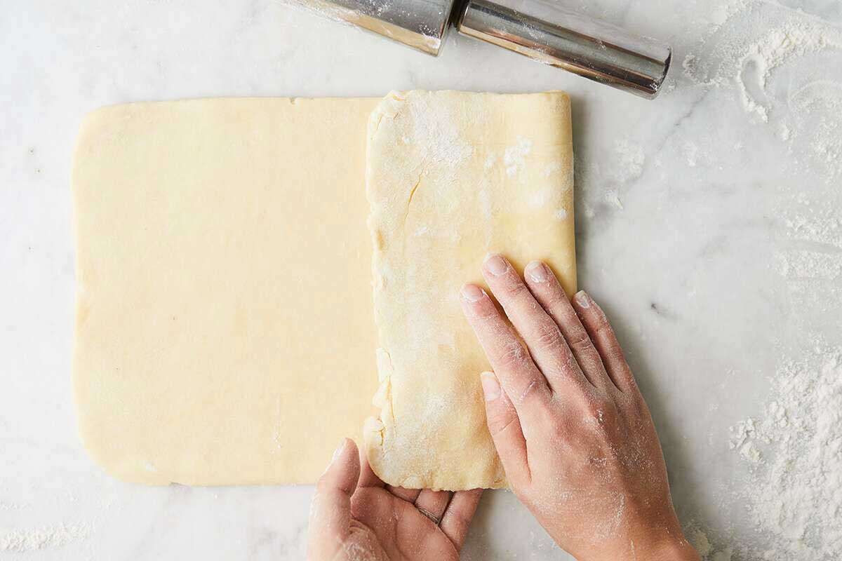Hands folding laminated pastry dough into thirds