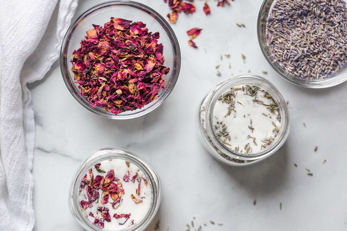 Rose petals on a plate next to a bowl of lavender flowers, ready to make infused sugar