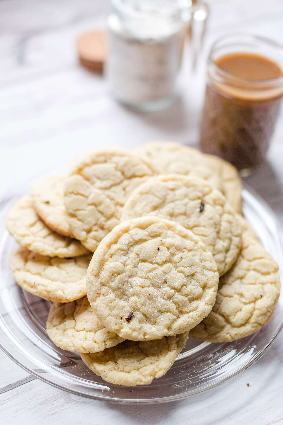 A plate of vanilla bean sugar cookies next to a cup of coffee and a jar of vanilla sugar