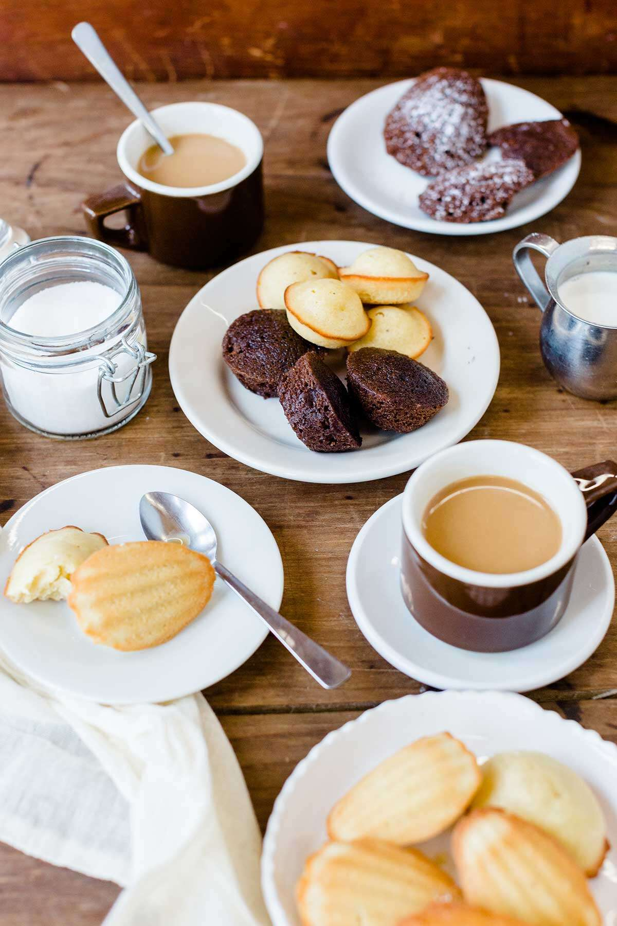 A table arranged with a platter of madeleines, coffee cups, plates, spoons, and a jar of sugar
